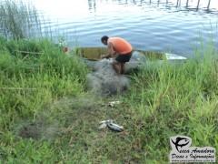 Homem retirando o material ilegal do barco (Foto Divulgação: Policia Ambiental)