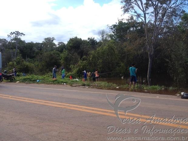 Moradores pescam na beira da estrada com a cheio do Rio Madeira em RO