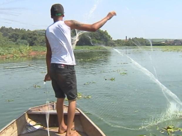 Pescador artesanal lanca rede no rio tiete
