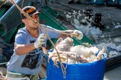Trabalhador de cooperativa descarregando pescado