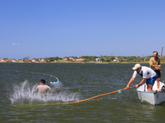 Homens praticando pesca com rede de cerco